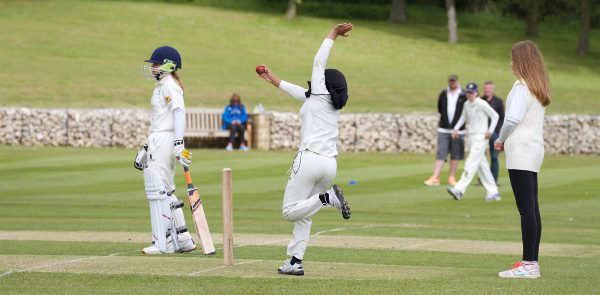 girls-cricket bowler in a cricket match delivers the ball, as the umpire watches on