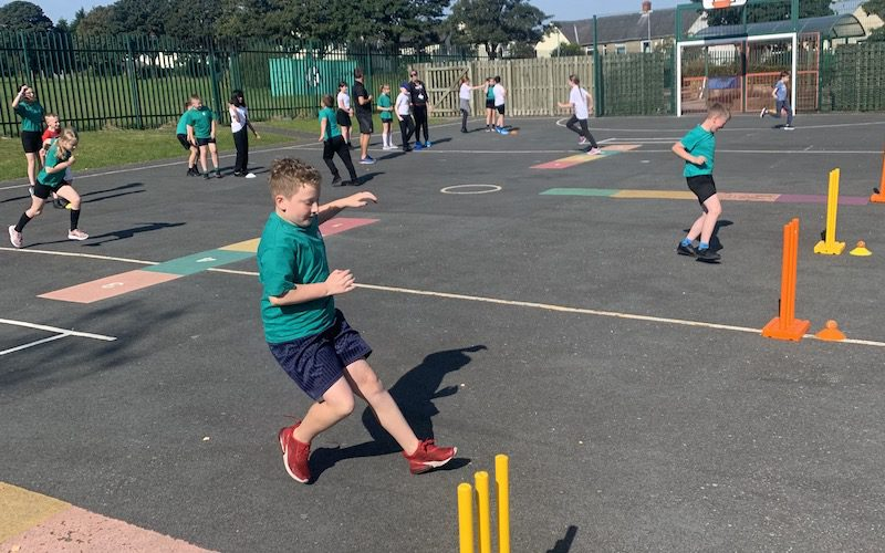 schoolchildren play cricket in the playground