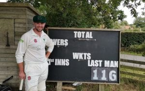 Great Habton Cricket Club player poses in front a scoreboard